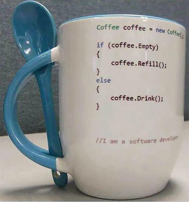 A white mug with pseudocode (perhaps Java?) on it; its handle is blue, and there is a blue spoon slotted through holes in the top and bottom of the handle so that it is readily available for use